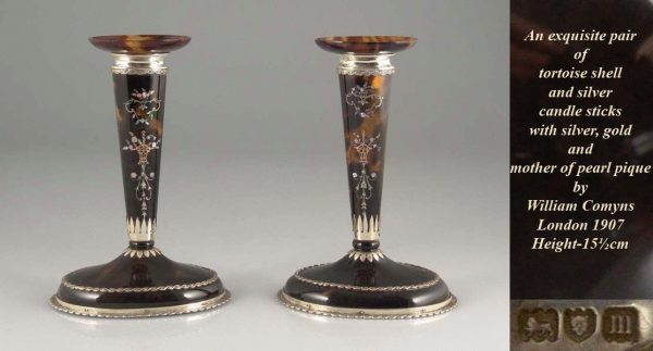 A pair of tortoise shell and silver candle sticks